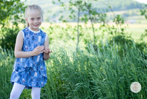 Mädchen mit blauem Kleid auf grüner Wiese