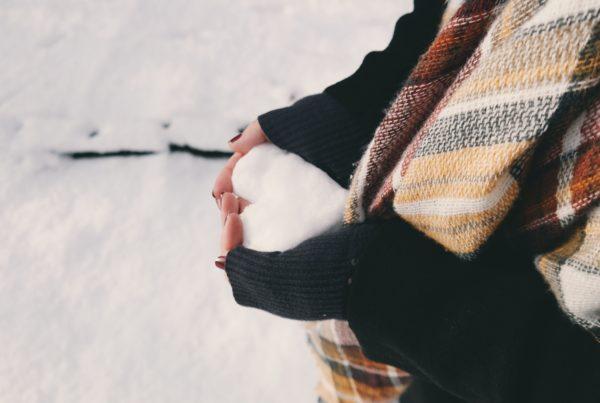 Frau hält Schnee Herz